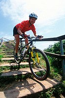 Woman mountain biker rides down stairs