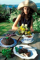Scottish pudding on garden table, young woman behind