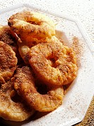 Deep-fried apple rings with cinnamon sugar on white plate