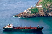 Boat leaving Saint John's Port. Remains of the Fort Amherst on the cape. Newfoundland and Labrador. Canada