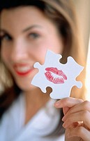 Girl showing a jigsaw puzzle piece with a kiss