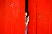 Chinese girl behind the red door. Port Louis. Mauricius