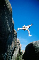 Boy jumping over abyss