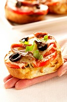 Hand holding mini-pizza with tomatoes, olives and anchovies
