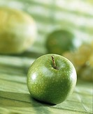 Granny Smith apple on green background