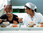 Anorexic woman (left)  being counselled  as  she eats a meal at a clinic. Anorexia nervosa is a psychological disorder in which sufferer...
