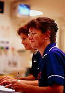 Hospital  nurses  writing  notes. Photographed at St Richard´s Hospital, Chichester, West Sussex, England.