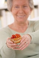 Sweet food. Elderly woman holds a strawberry-topped cake.