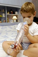 ASTHMA, CHILD<BR>Model.<BR>Boy holding a Babyhaler (inhalation chamber for infants and children). Asthma treatment.