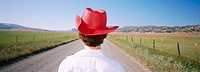 Woman with red cowboy hat on dirt road, California