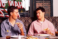 Fifteen-year-old boys enjoy a pizza.