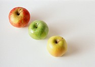 Three apples, red, green, yellow, in diagonal line, against white background
