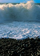 Wave crashing on pebbly beach