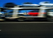 Truck carrying cars in motion, blurry