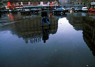 Person walking through square on wet ground with reflection