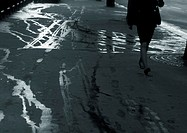 Woman walking on sidewalk with wet streaks, lower section