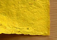 Corner of yellow-colored, recycled paper, close-up