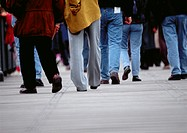 Lower section of people walking on sidewalk, blurred