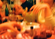 People eating at table in restaurant, blurred