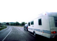 Car with mobile home driving on road, blurry