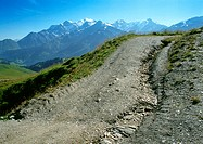 France, Alpes, dirt uphill road with snow-covered mountains in background