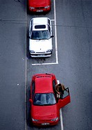 Red and white cars parked on asphalt, birdseye view