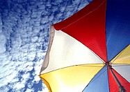 Multi-colored parasol, blue sky with clouds in background, low angle view