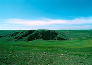 Mongolia, grassy plain with grass covered cliff