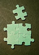 Four connected puzzle pieces and one separate piece, close-up