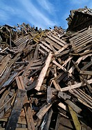 Large heap of wooden planks and pallets, blue sky in background