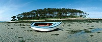 France, boat on seashore at low tide, island in background, panoramic view