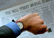 Watch on wrist, newspaper in background