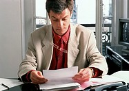 Man sitting at desk, reading document (thumbnail)