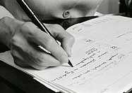 Hand writing on agenda, close-up, b&amp;w
