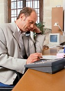 Man sitting at desk, telephoning, side view