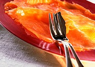 Slices of smoked salmon on plate with silverware, close-up
