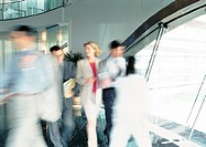 People walking inside office building, blurred