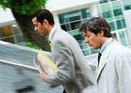 Two businessmen walking up stairs, upper section, blurred