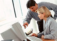 Businessman and businesswoman looking at computer screen