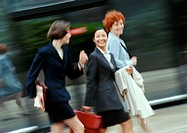 Three businesswomen walking in street, smiling, blurred