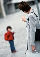 Businesswoman waving to child