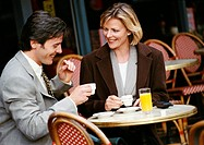 Businessman and businesswoman having coffee at cafe terrace