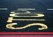 'Stop' text painted on asphalt, close-up