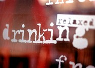 'Relaxed, drinking' text on window, close-up