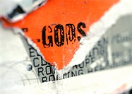'Gods' text printed on torn poster, close-up