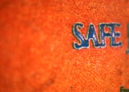 'Safe' text on orange surface, close-up