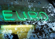 'Euro' text, neon sign, and tree reflection on glass, close-up
