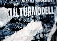 'Cultural model' text in German printed on torn poster, close-up