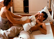 Couple having pillow fight on bed