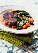 Steak with asparagus and carrots on plate, close-up